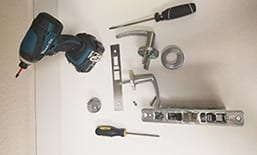 Drill with 2 screw drivers and some parts of a door
